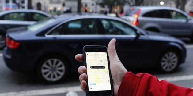 An UBER application is shown as cars drive by in Washington, DC on March 25, 2015. Uber said it was ramping...