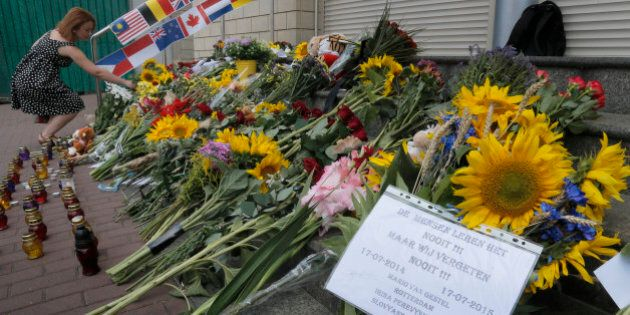 People lay flowers at the Netherlands Embassy for the Malaysia Airlines Flight MH17 crash victims, in...