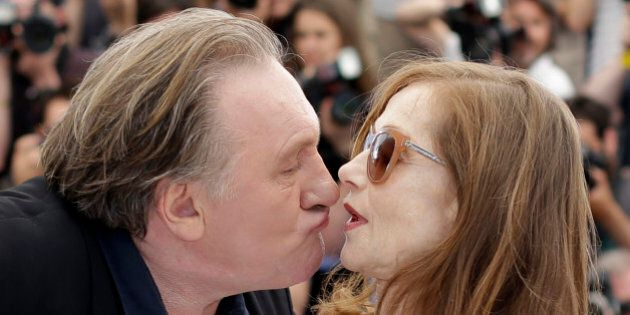 Actor Gerard Depardieu, left, tries to kiss actress Isabelle Huppert during a photo call for the film...