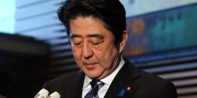 Japanese Prime Minister Shinzo Abe looks down as he arrives at his official residence in Tokyo to speak...