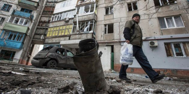A man walks by a burned car and a piece of exploded Grad missile, outside an apartment building in Vostochniy...