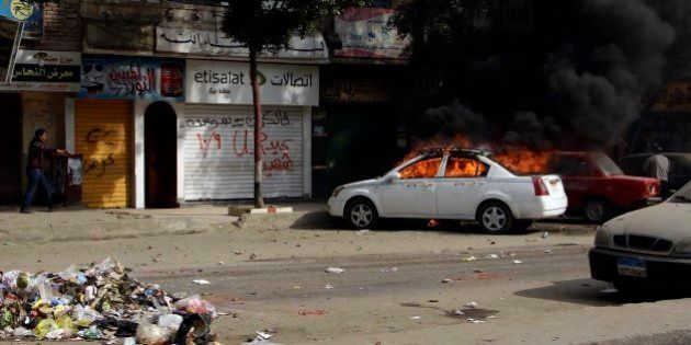 A taxi burns during clashes with Egyptian security forces in the Cairo suburb of Matariyah, Egypt, Sunday,...