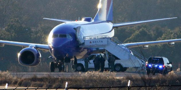 Law enforcement officials stand beneath a Southwest Airlines airplane on the tarmac at Hartsfield-Jackson...