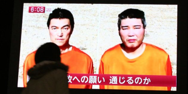 A passer-by watches a TV news program reporting two Japanese hostages, Kenji Goto, left, and Haruna Yukawa,...