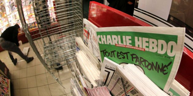 In this photo made with a fish-eye lens, people wait to buy the latest issue of Charlie Hebdo newspaper...