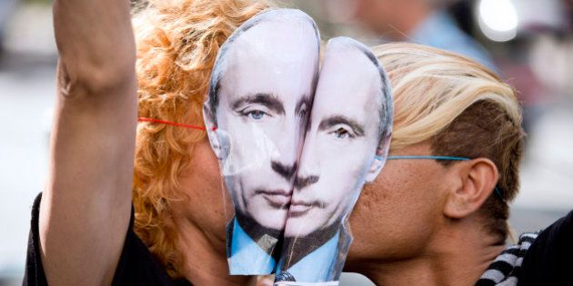 Demonstrators wearing masks depicting Russian President Vladimir Putin kiss as they take part in a rally...