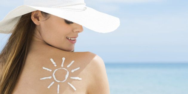Young Woman Looking At Sun Drawn On Her Back With Suntan Lotion
