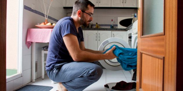 Close-up of man wearing blue pijama pulling towel from washing machine in