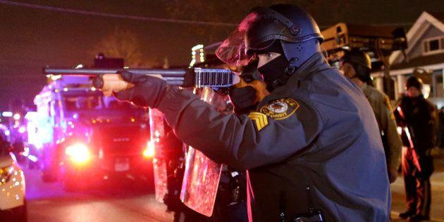 FERGUSON, MO - NOVEMBER 24: A police officer points a shotgun at protestors during a demonstration on...