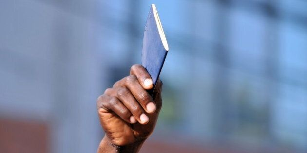 A Haitian holds up his passport at the passport and immigration centre in Port-au-Prince on January 22,...