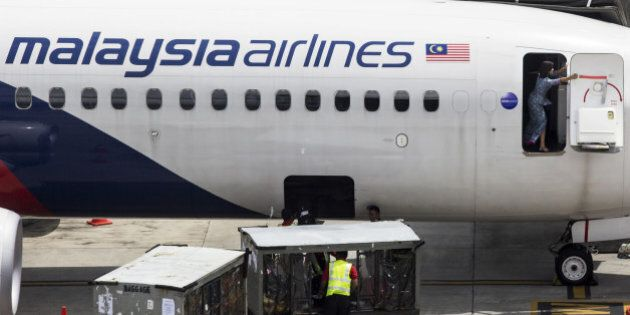 A flight attendant reaches out to close the door of an aircraft operated by Malaysian Airline System...