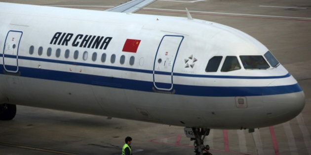 A ground staff member works towards an Air China Ltd. aircraft at Shanghai Pudong International Airport...