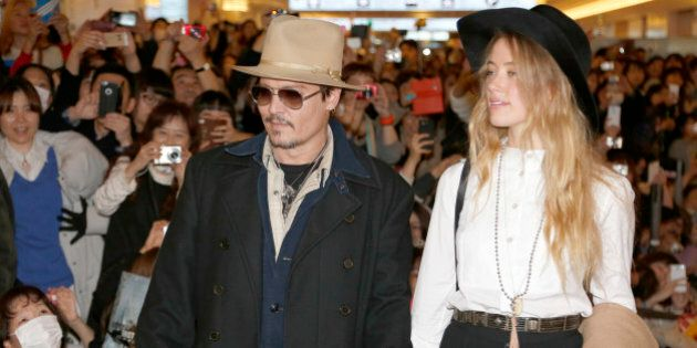 U.S. actor Johnny Depp and his fiancee Amber Heard arrive at Haneda international airport in Tokyo Monday, Jan. 26, 2015 for his latest film