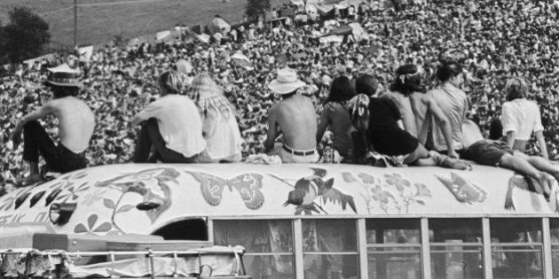 Fans sitting on top of a painted bus at the Woodstock Music Festival, Bethel, New York, 15th-17th August...