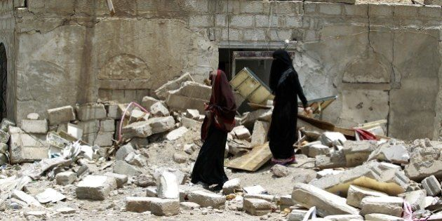 Yemeni women walk amidst the rubble of houses destroyed by Saudi-led air strike on a residential area...