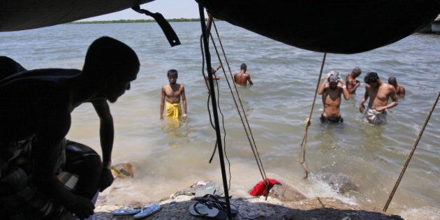Bangladeshi men wash themselves in the sea at a temporary shelter in Langsa, Aceh province, Indonesia...