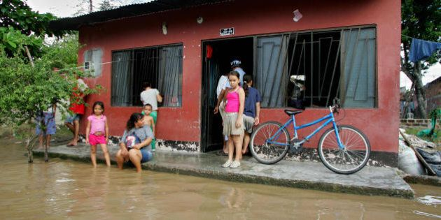 A Colombian family stands at the entrance of their home after heavy rains flooded their neighborhood...