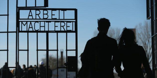 ORANIENBURG, GERMANY - MARCH 18: Visitors walk through the infamous 'Arbeit Macht Frei' ('Work Makes...