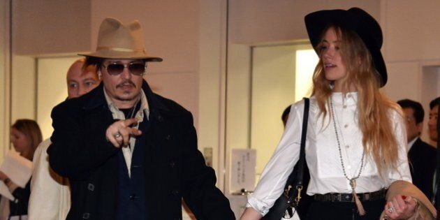 US actor Johnny Depp (L), accompanied by his fiancee US actress and model Amber Heard (R), arrive at Tokyo International Airport on January 26, 2015 for the Japan premiere of his latest movie 'Mortdecai'.  The action comedy movie will be screened in Japan from February 6.  AFP PHOTO        (Photo credit should read YOSHIKAZU TSUNO/AFP/Getty Images)