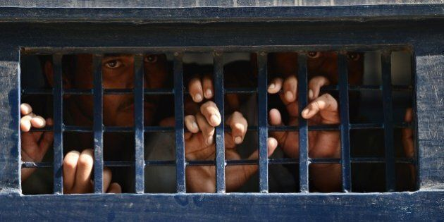 Arrested Pakistani opposition workers look out from a prison van following a protest at the court area...