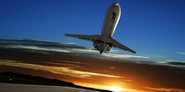 corporate jet airplane landing on runway at sunset
