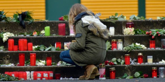 A student kneels down at candles placed in front of the Joseph-Koenig Gymnasium in Haltern, western Germany,...
