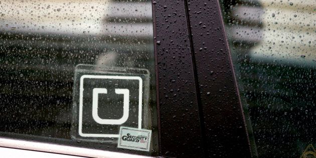 The Uber Technologies Inc. logo is displayed on the window of a vehicle after dropping off a passenger at Ronald Reagan National Airport (DCA) in Washington, D.C., U.S., on Wednesday, Nov. 26, 2014. Uber Technologies Inc. investors are betting the five-year-old car-booking app is more valuable than Twitter Inc. and Hertz Global Holdings Inc. Photographer: Andrew Harrer/Bloomberg via Getty Images