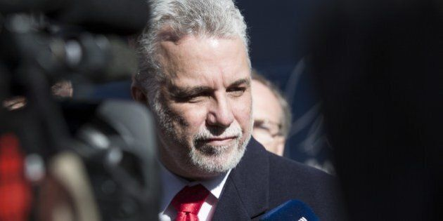 Quebec Liberal leader, Philippe Couillard, speaks to reporters in front of his campaign bus April 1,...