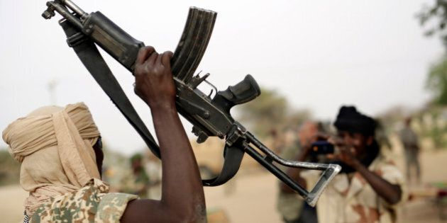 A Chadian soldier raises his automatic weapon to have his picture taken by another soldier in the Nigerian...