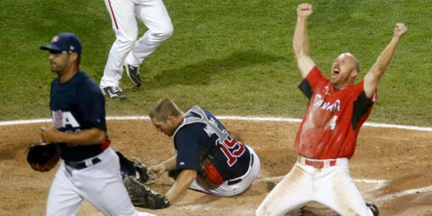 Canada's Peter Orr, right, scores the game-winning run under the tag of United States catcher Thomas...
