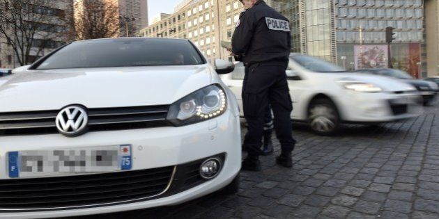 Police officers check the documents of a driver as they enforce pollution control measures in Paris on...