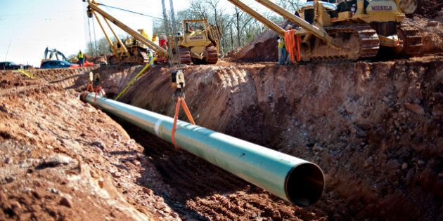 A sixty-foot section of pipe is lowered into a trench during construction of the Gulf Coast Project pipeline...