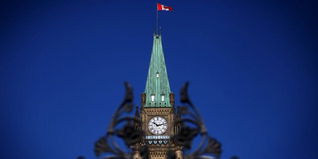 The Canadian flag flies above Parliament Hill in Ottawa, Ontario, Canada, on Tuesday, Feb. 11, 2014. Canadian Finance Minister Jim Flaherty ramped up efforts to return the country to surplus in a budget that raises taxes on cigarettes and cuts benefits to retired government workers while providing more aid for carmakers. Photographer: Cole Burston/Bloomberg via Getty Images