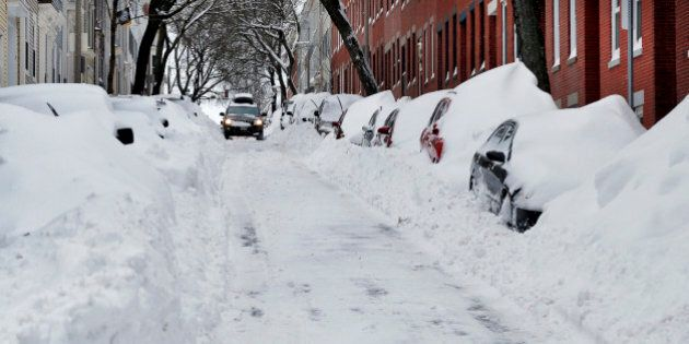 A car makes its way down a street filled with snowed-in vehicles in Boston's Charlestown section, Wednesday,...
