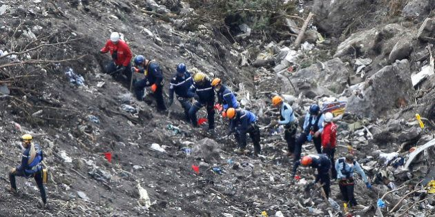 Rescue workers work at the Germanwings passenger plane crash site near Seyne-les-Alpes, France, Thursday,...