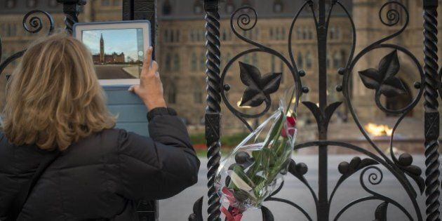 A lady takes a photo through the Queen's Gate at Canada's House of Parliament in Ottawa on Thursday evening...