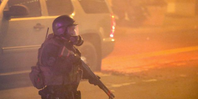 FERGUSON, MO - NOVEMBER 25: Police try to control demonstrators with tear gas during a protest on November...