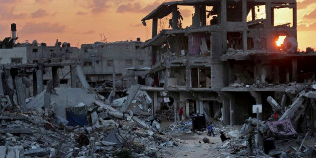 Palestinians walk during the sunset between the rubble of their destroyed building in Shijaiyah neighborhood...