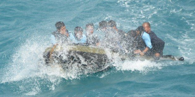 Indonesian navy divers head to navy vessel KRI Banda Aceh as they conduct operations to lift the tail...