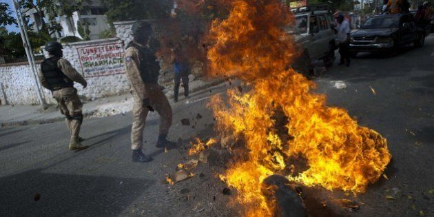 Haitian police remove a barricade of burning tires placed by anti-government protesters during a march...