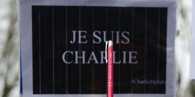 A woman holds a pen in front of a sign reading 'Je suis Charlie' (I am Charlie) during a Unity march...
