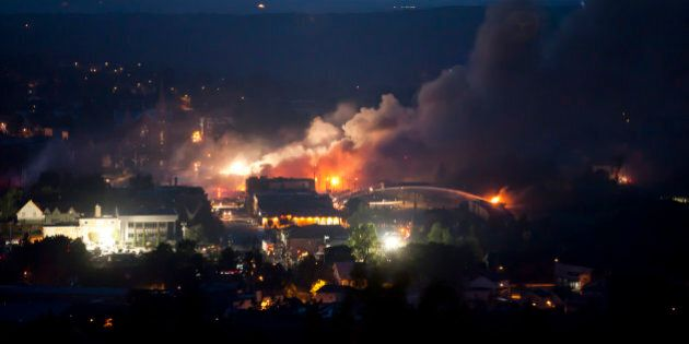 Firefighters douse blazes after a freight train loaded with oil derailed in Lac-Megantic in Canada's Quebec province on July 6, 2013, sparking explosions that engulfed about 30 buildings in fire.  At least 80 people are missing after a driverless oil tanker train derailed and exploded in the small Canadian town of Lac-Megantic, destroying dozens of buildings, a firefighter back from the scene told AFP.    AFP PHOTO /  François Laplante-Delagrave        (Photo credit should read François Laplante-Delagrave/AFP/Getty Images)