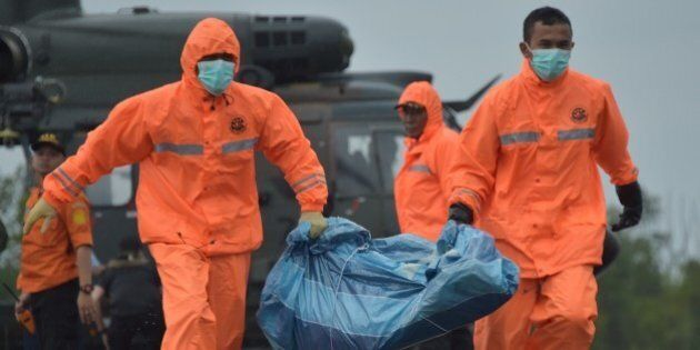 Members of an Indonesian search and rescue team carry items for investigation, found during the search...
