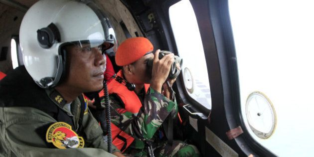 Crew members of Indonesian Air Force NAS 332 Super Puma helicopter look out of the windows during a search...
