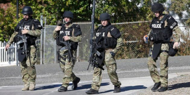 Law enforcement officers dressed in tactical gear leave the Gold County Fairgrounds to help in the search...