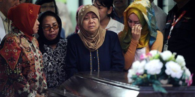 SURABAYA, INDONESIA - JANUARY 01: Hayati Lutfiah Hamid's (C), the mother of the first identified victim...