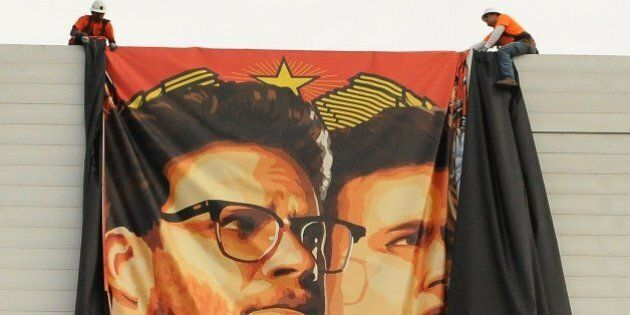 Workers remove a poster-banner for 'The Interview' from a billboard in Hollywood, California, December...