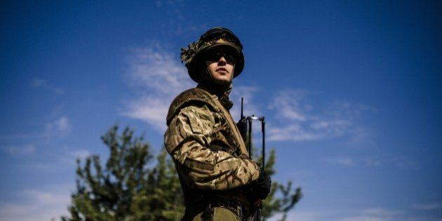 A Ukrainian soldier stands guard at a checkpoint on a road near the city of Dnepropetrovsk on August...