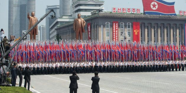 North Koreans wave flags and walk with statues of former leaders Kim Il-Sung and Kim Jong-Il during a...