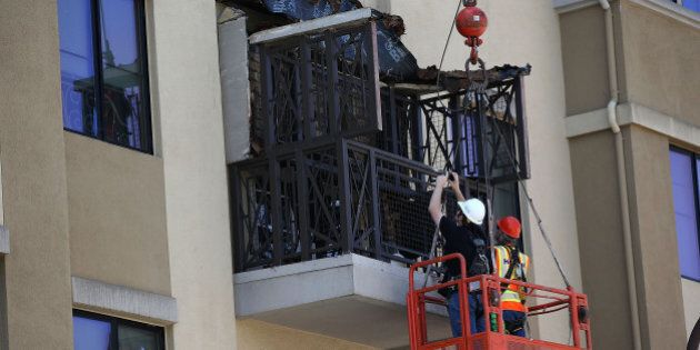BERKELEY, CA - JUNE 16: Workers inspect a balcony that collapsed at an apartment building near UC Berkeley...